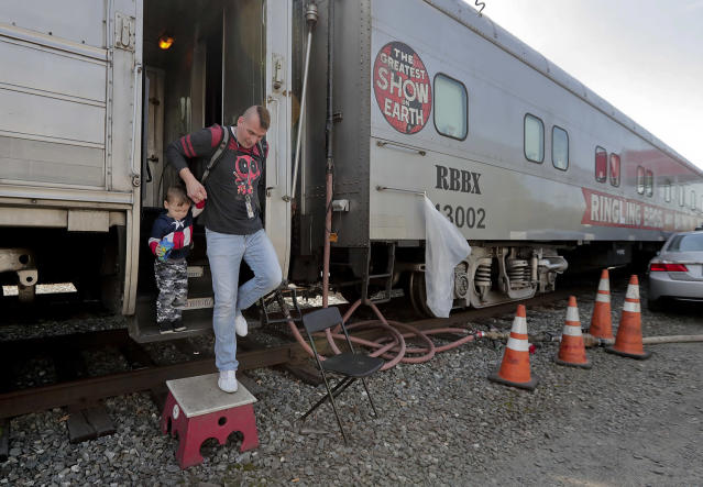 """<p>Boss clown Sandor Eke helps his 2-year-old son. Michael Eke step off the Ringling Bros. circus red unit's traveling train parked in a rail yard as they head to the arena for a show, Thursday, May 4, 2017, in Providence, R.I. Someday, he plans to teach his son juggling and other circus skills, but Eke knows he may never join the circus. Eke's wife, a former circus aerialist, has already established their new home in Las Vegas. When the circus closes, Eke hopes to get a job as a """"flair"""" bartender there, doing tricks like juggling bottles, but he wonders how life will change. """"My normal life is this. My normal life is going on the train, going every week to a different city. It's crazy how much I love circus,"""" Eke says. (Photo: Julie Jacobson/AP) </p>"""