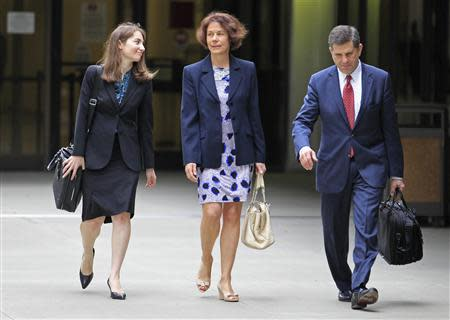 Attorney Aaron Marcu (R) who represents Raoul Weil, a former high-ranking UBS banker charged with tax fraud by U.S. authorities, who is pending release on bail of $10.5 million, walks with Weil's wife, Susan Lerch Weil (C) and attorney Kimberly Zelnick as they leave federal court in Fort Lauderdale, Florida December 16, 2013. REUTERS/Joe Skipper