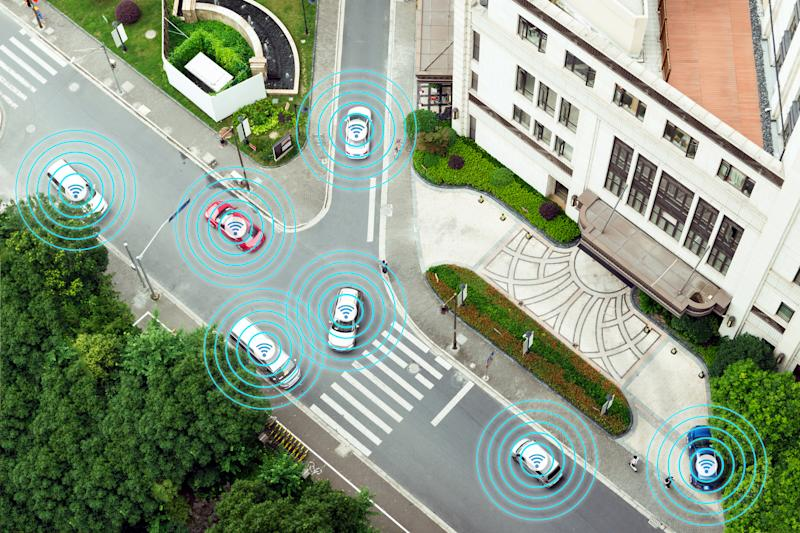 Overhead image of cars on road with circles around them on a street with tress and buildings.