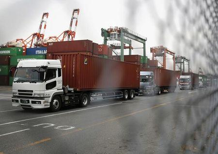 Trucks line up after they loaded containers at a port in Tokyo