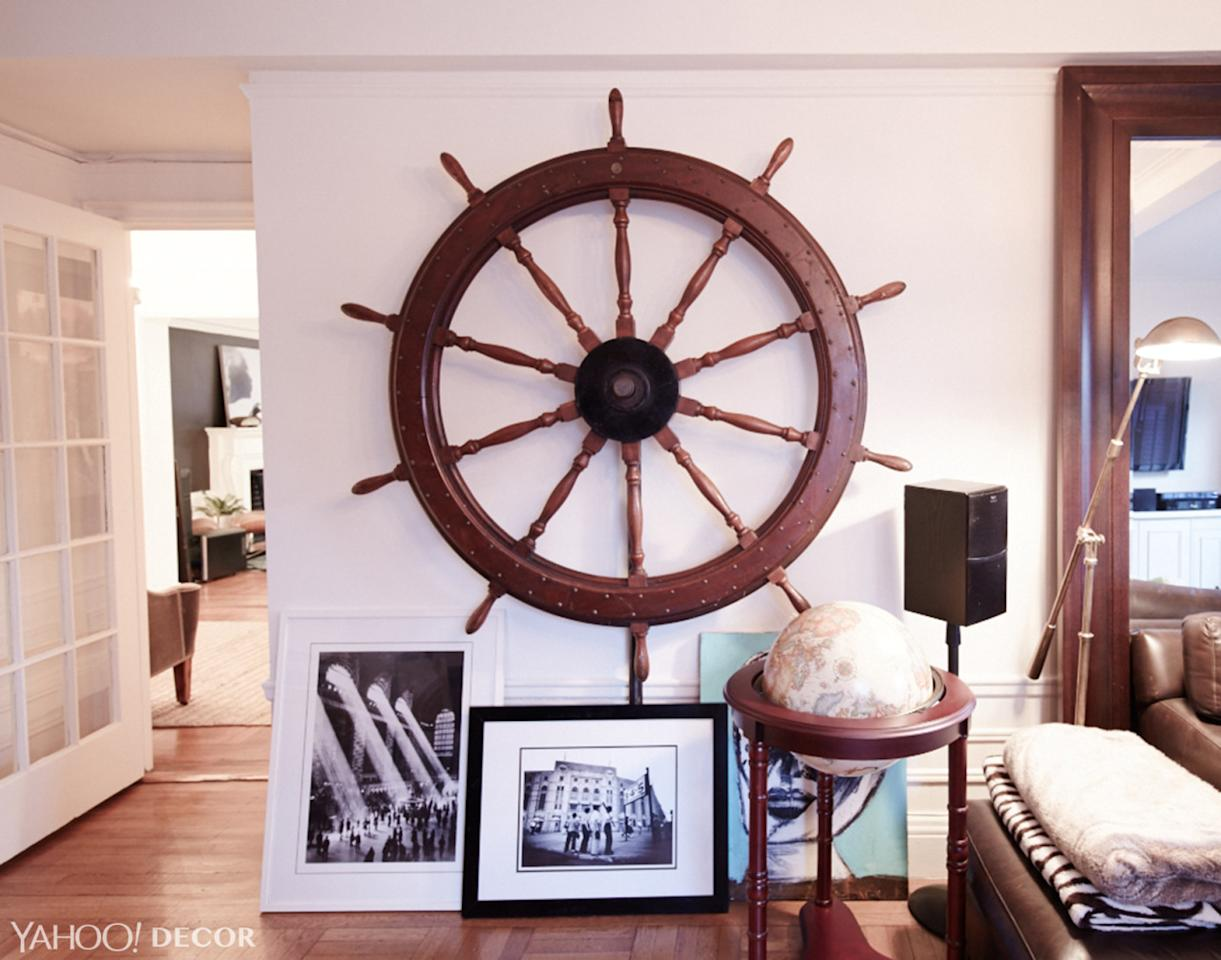 <p>The ship's wheel came from an office supply store and comes from a Philadelphia ship that dates back to the early 1900s.Neff decided to mount it on the wall and leave space underneath to lean framed artwork on the floor — including a mixed-media painting by Eddie Martinez and some artwork Neff's roommate found on the streets of NYC. The globe was a gift that started Neff's love for collecting.</p>