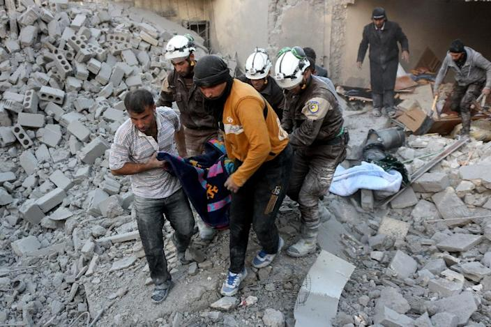 Syrian volunteers evacuate a victim from the rubble of a building following reported airstrikes on Aleppo's rebel-held district of al-Hamra, on November 20, 2016 (AFP Photo/Thaer Mohammed)