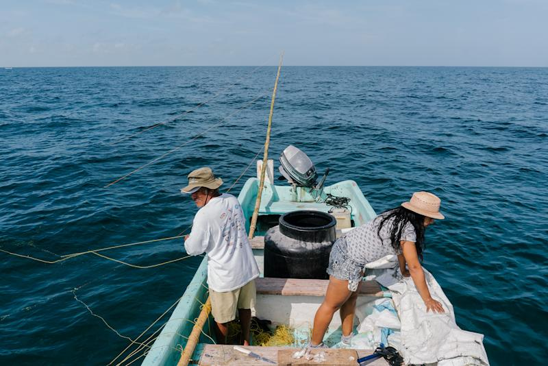 Cob Reyes and Plata Diaz scout the waters for octopuses to catch. | Jake Naughton for TIME