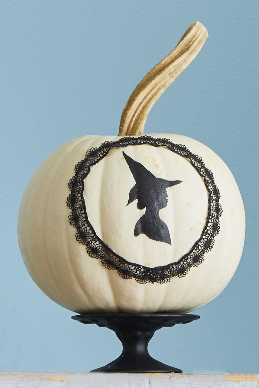"""<p>You can never go wrong with a witch theme when it comes to Halloween. Paint a <a href=""""http://clipart-library.com/free/halloween-witch-silhouette-templates.html"""" rel=""""nofollow noopener"""" target=""""_blank"""" data-ylk=""""slk:witch silhouette"""" class=""""link rapid-noclick-resp"""">witch silhouette </a>on a white pumpkin, then cut out the middle of black doily, and hot glue the frame around your witch.</p><p><a class=""""link rapid-noclick-resp"""" href=""""https://www.amazon.com/Darice-Black-Paper-Doilies-Piece/dp/B073SH49GJ/?tag=syn-yahoo-20&ascsubtag=%5Bartid%7C10070.g.331%5Bsrc%7Cyahoo-us"""" rel=""""nofollow noopener"""" target=""""_blank"""" data-ylk=""""slk:SHOP BLACK DOILIES"""">SHOP BLACK DOILIES</a></p>"""