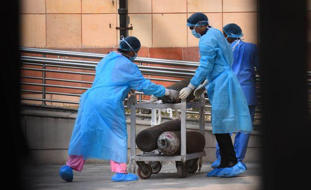 Medical workers draw a cart with oxygen cylinders outside the Covid-19 ward, at Lok Nayak Jai Prakash Narayan Hospital, on July 1, 2020 in New Delhi.