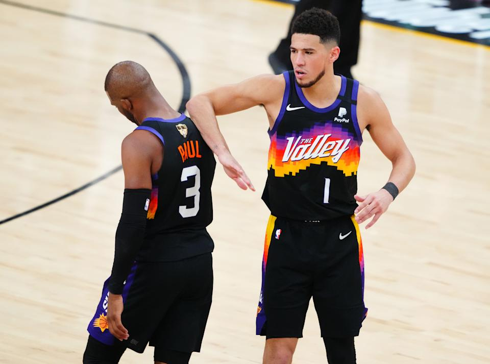 Phoenix Suns guard Devin Booker (1) reacts with guard Chris Paul (3) against the Milwaukee Bucks during the second half in game one of the 2021NBA Finals at Phoenix Suns Arena. Mandatory Credit: Mark J. Rebilas-USA TODAY Sports