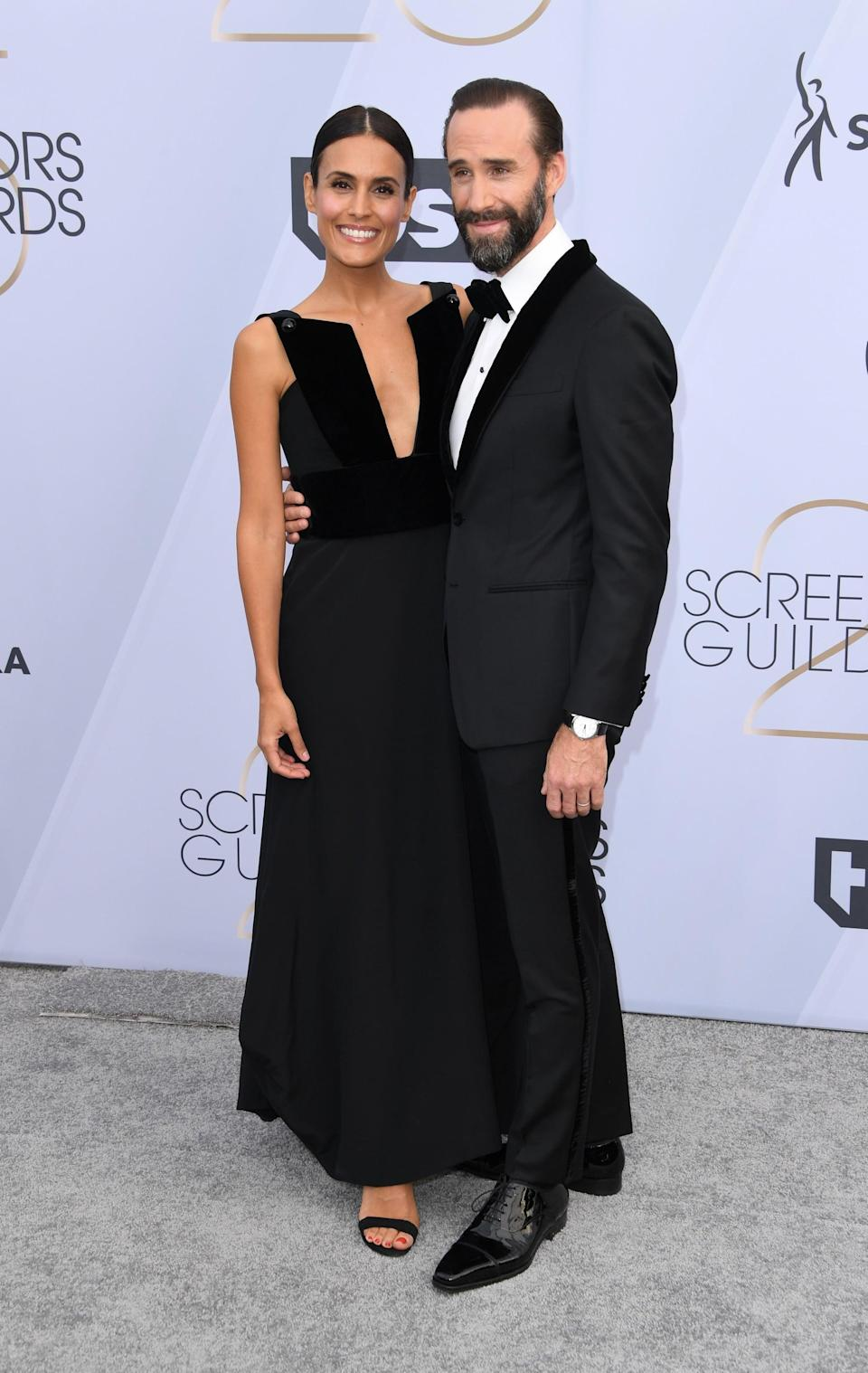 <p>Joseph wearing a black suit from Strong Suit by Ilaria Urbinati Collection and Montblanc cufflinks. Maria wearing a matching gown.</p>
