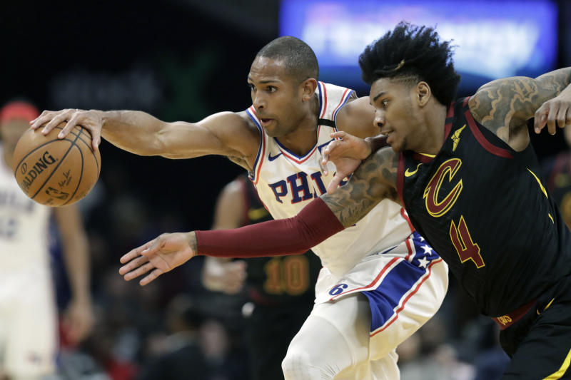 Philadelphia 76ers' Al Horford, left, and Cleveland Cavaliers' Kevin Porter Jr. battle for a loose ball in the first half of an NBA basketball game, Wednesday, Feb. 26, 2020, in Cleveland. (AP Photo/Tony Dejak)