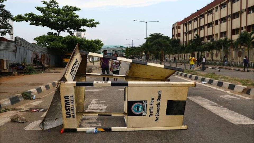 People walk near a roadblock as authorities imposed a round-the-clock curfew on the Nigerian state of Lagos, in response to protests against alleged police brutality, Nigeria October 20, 2020.