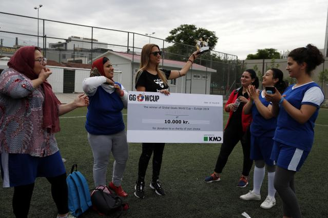 In this Wednesday, May 22, 2019 photo, Katerina Salta, Sport for Protection Program Manager holds the Global Goals World Cup trophy as members Hestia FC Women's Refugee Soccer team applaud in Athens. Many of the players at Hestia FC weren't allowed to play or even watch soccer matches in their home countries. Hestia FC was set up by the Olympic Truce Centre, a non-government organization created in 2000 by the International Olympic Committee and Greek Foreign Ministry. (AP Photo/Thanassis Stavrakis)