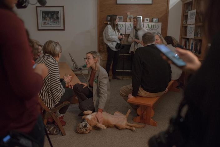 Abigail Bessler pets a dog while speaking with supporters at a Hotdish House Party. | September Dawn Bottoms for TIME