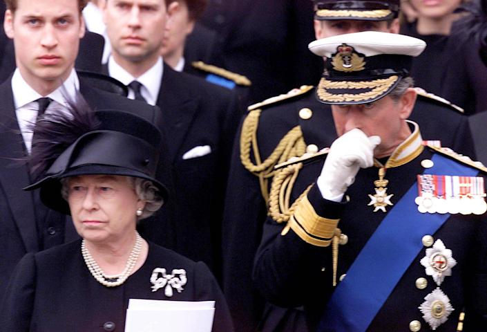 Britain's Queen Elizabeth, left, foreground, watches as the coffin containing the body of the Queen Mother is put into a hearse following her funeral service in Westminster Abbey. The Prince of Wales is at right. Background left is Prince William, and next to him is Prince Edward.   (Photo by PA Images via Getty Images)