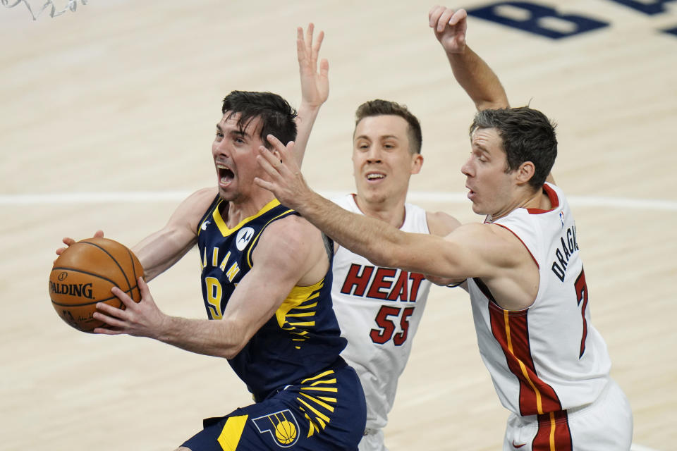 Indiana Pacers guard T.J. McConnell (9) drives between Miami Heat defenders Duncan Robinson (55) and Goran Dragic (7) during the first half of an NBA basketball game in Indianapolis, Wednesday, March 31, 2021. (AP Photo/AJ Mast)