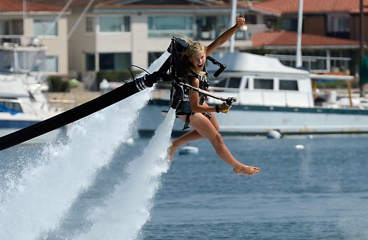 NEWPORT BEACH, CA - SEPTEMBER 25:  Johnnie Faye Carthwright, 20, a flight instructor assistant, demonstrates flying using a JetLev, a water-powered Jetpack flying machine in the Newport Beach harbor on September 25, 2012 in Newport Beach, California. Dean O'Malley, president of JetLev, will attempt to establish a new world record for flight of the JeLev by making a 26 mile open ocean crossing from Newport Beach to Avalon, Catalina Island on September, 29, 2012.  (Photo by Kevork Djansezian/Getty Images)