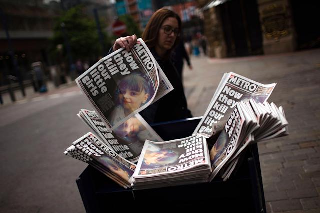 <p>A woman picks a newspaper reporting the news on the suicide attack at a concert by Ariana Grande that killed more than 20 people as it ended Monday night in central Manchester, Britain, Wednesday, May 24, 2017. (AP Photo/Emilio Morenatti) </p>