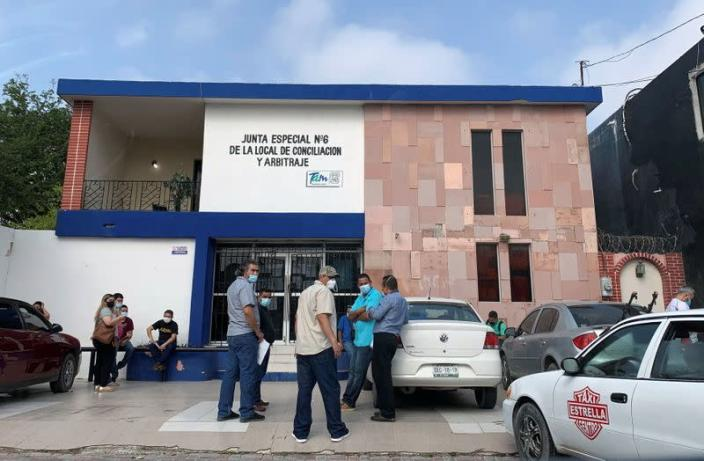 Workers aiming to resolve labor disputes wait outside a Conciliation and Arbitration Board, in Matamoros