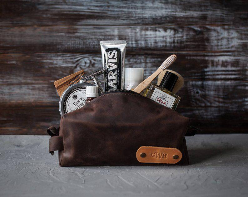 """<p><strong>SoGoodSoWood</strong></p><p>etsy.com</p><p><strong>$26.62</strong></p><p><a href=""""https://go.redirectingat.com?id=74968X1596630&url=https%3A%2F%2Fwww.etsy.com%2Flisting%2F615734243%2Fpersonalized-leather-dopp-kit-mens&sref=https%3A%2F%2Fwww.womansday.com%2Frelationships%2Ffamily-friends%2Fg27467309%2Fpersonalized-gifts-for-dad%2F"""" rel=""""nofollow noopener"""" target=""""_blank"""" data-ylk=""""slk:Shop Now"""" class=""""link rapid-noclick-resp"""">Shop Now</a></p><p>Dad can store all of his essentials, from shampoo to shaving cream, in this leather dopp kit. With a choice of 10 different colors and up to two customizable stamps, you can design something totally original with him in mind.</p>"""