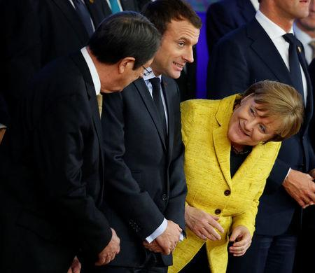 German Chancellor Angela Merkel laughs with French President Emmanuel Macron and President of Cyprus Nicos Anastasiades during a leaders photograph at the European Union leaders summit in Brussels, Belgium December 14, 2017. REUTERS/Phil Noble