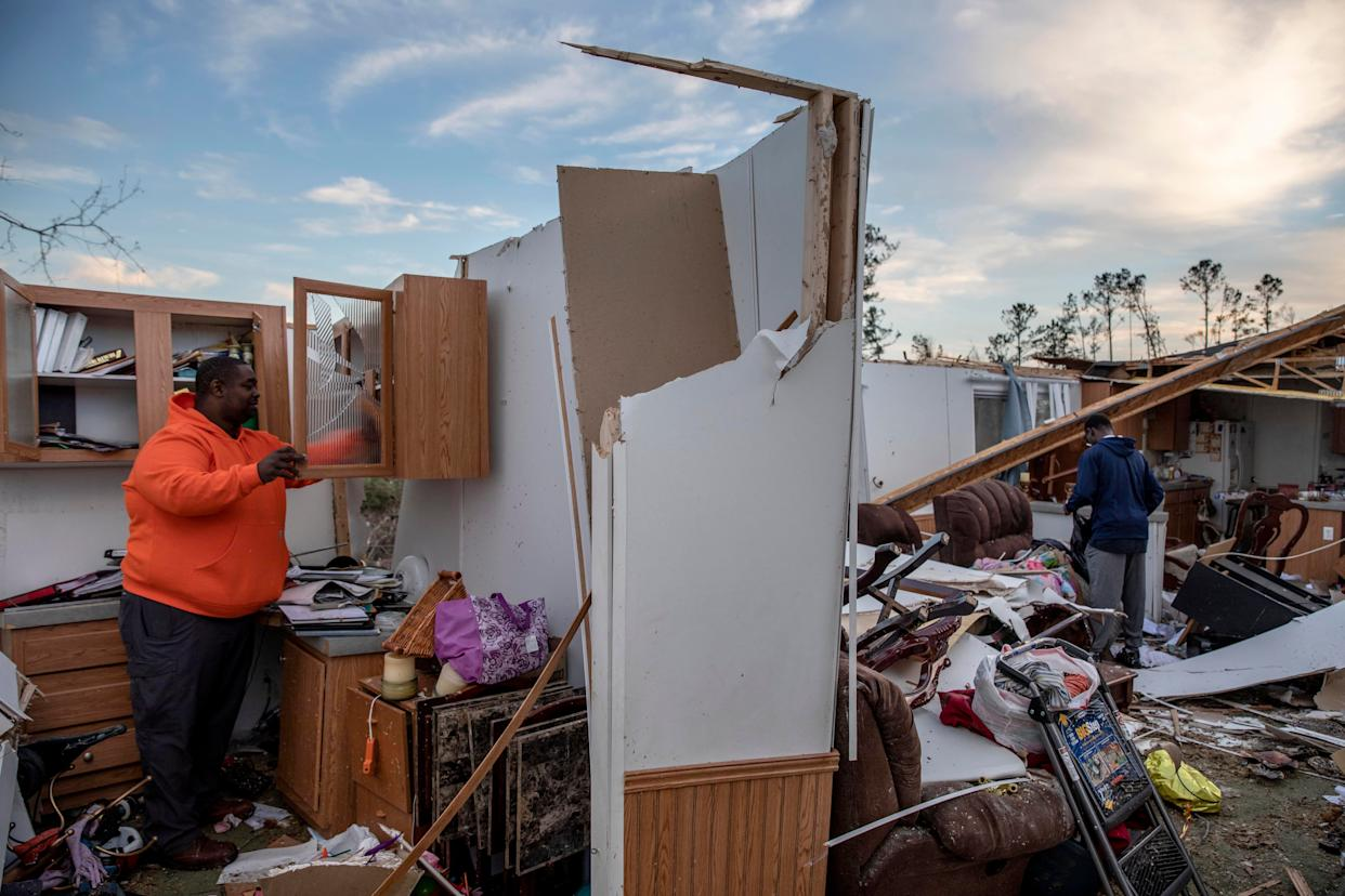 Granadas Baker, left, and son Granadas Jr. 18, right, retrieve personal items from the damaged home where they survived a tornado a day earlier in Beauregard, Ala., Monday, March 4, 2019. (AP Photo/David Goldman)