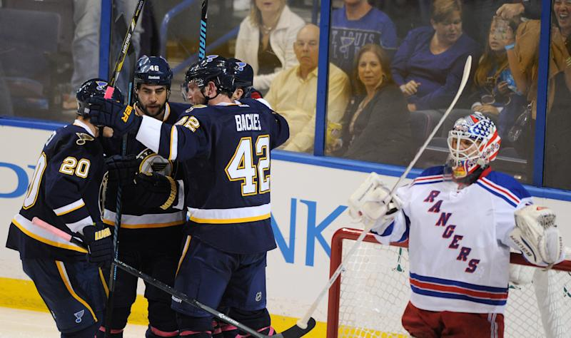 St. Louis Blues' David Backes (42) celebrates his goal with teammates Alexander Steen (20) and Roman Polak (46), of Czech Republic, as New York Rangers' goalie Martin Biron, right, looks away during the second period of an NHL hockey game on Saturday, Oct. 12, 2013, in St. Louis. (AP Photo/Bill Boyce)