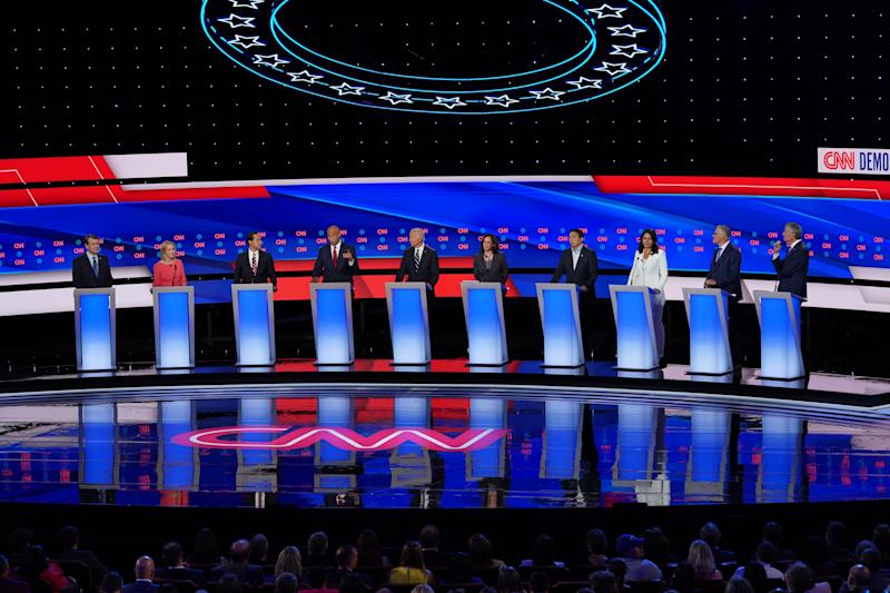 DETROIT, MICHIGAN - JULY 31: Democratic presidential candidate Sen. Cory Booker (D-NJ) (4th L) speaks while Sen. Michael Bennet (D-CO) (L-R), Sen. Kirsten Gillibrand (D-NY), former housing secretary Julian Castro, former Vice President Joe Biden, Sen. Kamala Harris (D-CA) , former tech executive Andrew Yang, Rep. Tulsi Gabbard (D-HI), Washington Gov. Jay Inslee, and New York City Mayor Bill De Blasio listen during Democratic Presidential Debate at the Fox Theatre July 31, 2019 in Detroit, Michigan. 20 Democratic presidential candidates were split into two groups of 10 to take part in the debate sponsored by CNN held over two nights at Detroit's Fox Theatre. (Photo by Scott Olson/Getty Images)