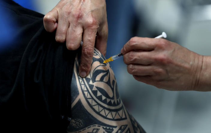 A tattooed person gets Pfizer vaccine at the National vaccination center in Prague, Czech Republic, Friday, April 9, 2021. On Friday the center, that is the biggest in the country, held its final trials before being able to vaccinate up to 10 000 people a day. (AP Photo/Petr David Josek)