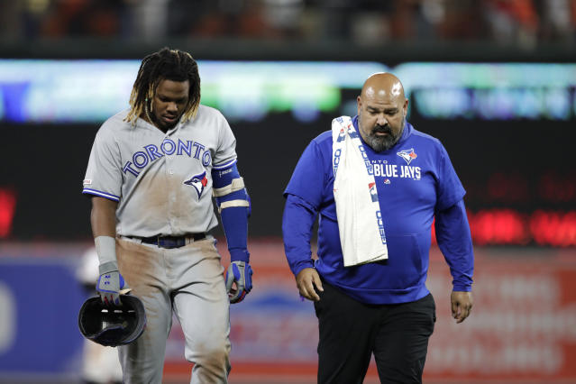 Toronto Blue Jays' Vladimir Guerrero Jr., left, walks with assistant athletic trainer Jose Ministral to the dugout after suffering an injury while reaching second base during the ninth inning of the team's baseball game against the Baltimore Orioles, Wednesday, Sept. 18, 2019, in Baltimore. The Blue Jays won 11-10. (AP Photo/Julio Cortez)