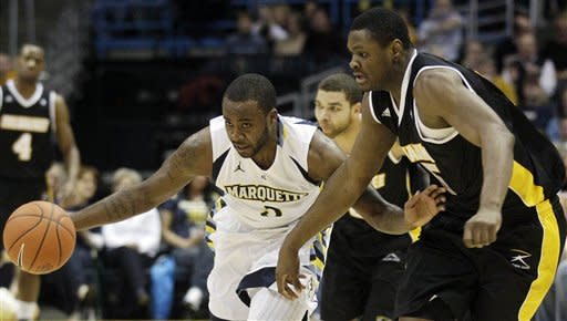 Marquette's Junior Cadougan (5) gets past Wisconsin Milwaukee's Demetrius Harris during the first half of an NCAA college basketball game on Thursday, Dec. 22, 2011, in Milwaukee. (AP Photo/Morry Gash)