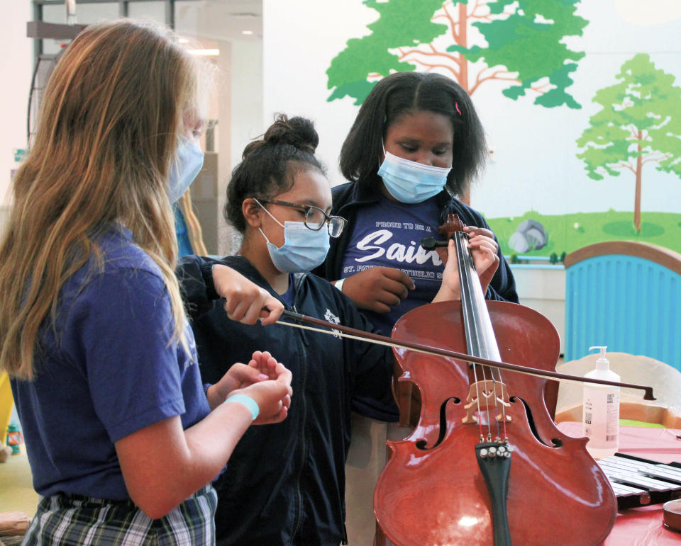 St. Patrick students Ann Larkin Vollor, Denise Quedado, and Madison Sloan learn about music during a field trip at the Missisippi Children's Meridian in Meridian, Miss on Friday, Sept. 17, 2021. (Bianca Moorman/The Meridian Star via AP)