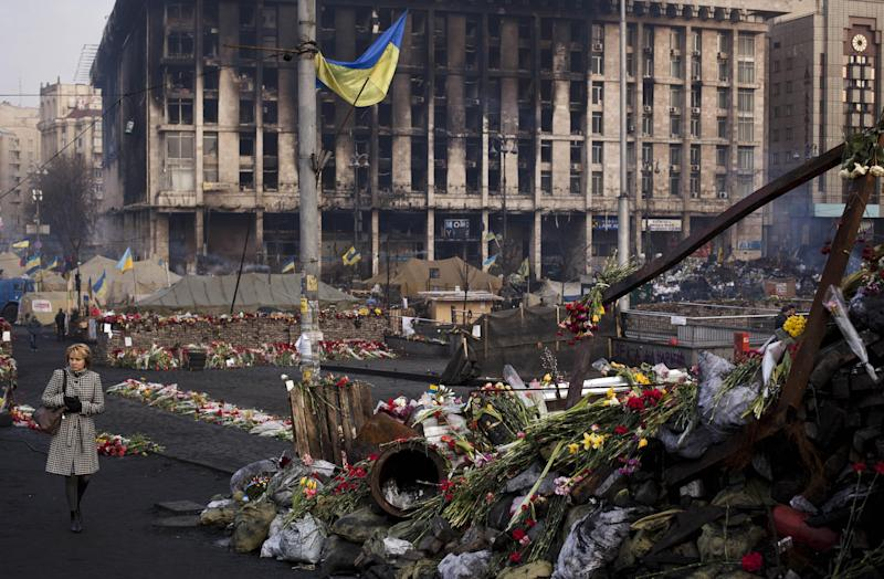 A woman walks past a barricade covered in flowers left to those killed in recent clashes in Kiev's Independence Square, Ukraine, Friday, March 7, 2014. In the background is the Trade Unions Building, which was damaged in a fire in late February. (AP Photo/David Azia)