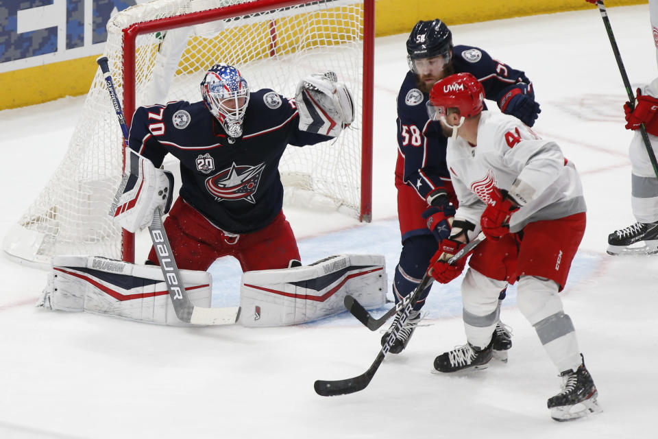 Columbus Blue Jackets' Joonas Korpisalo, left, makes a save as teammate David Savard, center, and Detroit Red Wings' Luke Glendening fight for position during the second period of an NHL hockey game Tuesday, March 2, 2021, in Columbus, Ohio. (AP Photo/Jay LaPrete)