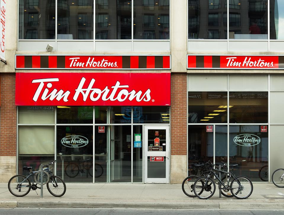 Toronto, Canada- 19th May 2014: The outside of a Tim Hortons Coffee Shop during the day. Bikes can be seen outside and people can be seen in the windows.