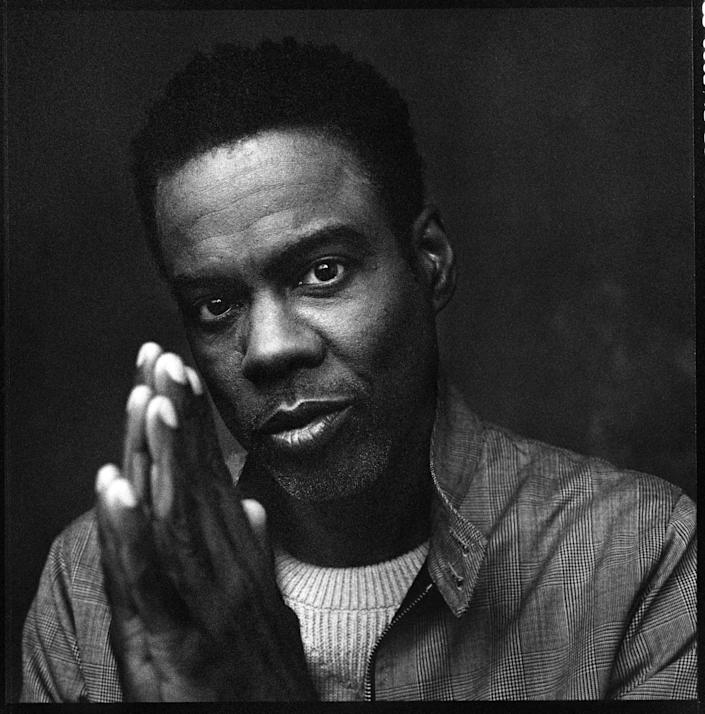 Chris Rock looks straight ahead with his hands in a praying motion.