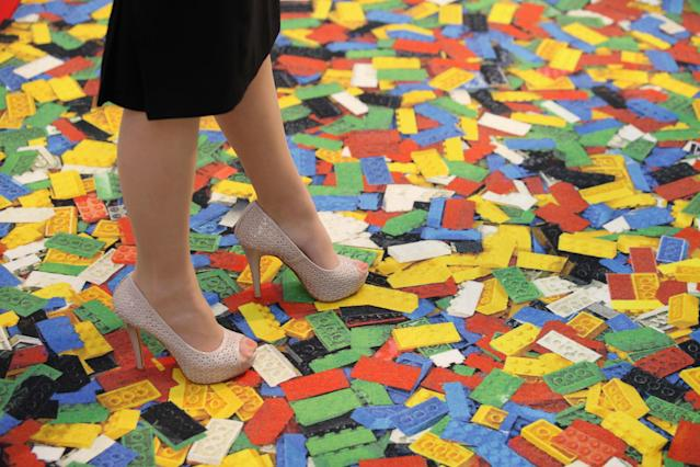 LONDON, ENGLAND - JANUARY 24: A woman stands on a carpet with a Lego brick design at the 2012 London Toy Fair at Olympia Exhibition Centre on January 24, 2012 in London, England. The annual fair which is organised by the British Toy and Hobby Association, brings together toy manufacturers with retailers from around the world. (Photo by Oli Scarff/Getty Images)