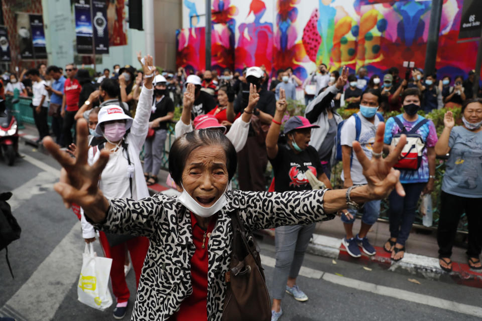 Pro-democracy protesters gather, flashing three-fingered salutes near a main shopping district in Bangkok, Thailand, Sunday, Oct. 25, 2020. Thousands of pro-democracy protesters gathered in Thailand's capital again on Sunday, seeking to keep up pressure on the government a day ahead of a special session of Parliament called to try to ease political tensions.(AP Photo/Gemunu Amarasinghe )