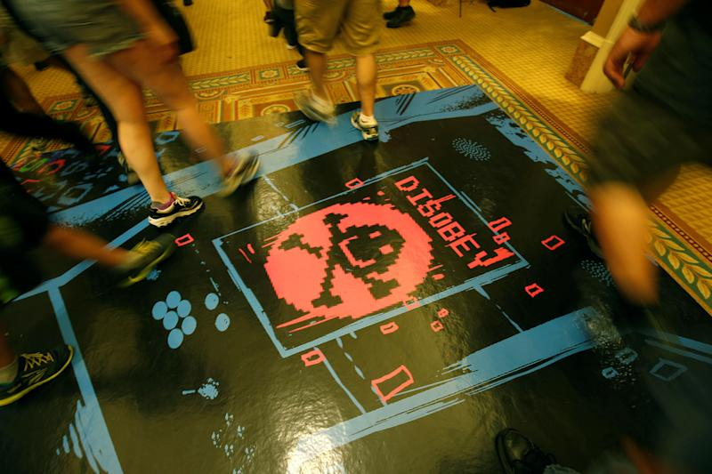 People walk past a floor graphic during the Def Con hacker convention in Las Vegas, Nevada, U.S. on July 29, 2017. REUTERS/Steve Marcus