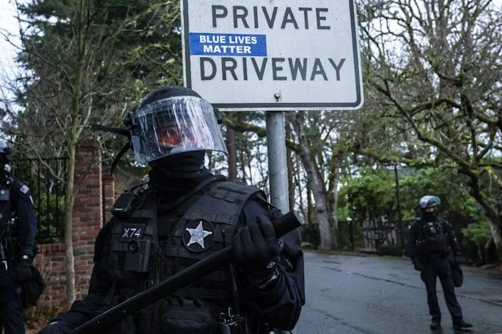 A Salem Police officer stands in front of a Blue Lives Matter sticker while guarding the governors mansion during a protest against COVID-19 restrictions on January 1, 2021 in Salem, Oregon. (Photo by Nathan Howard/Getty Images)