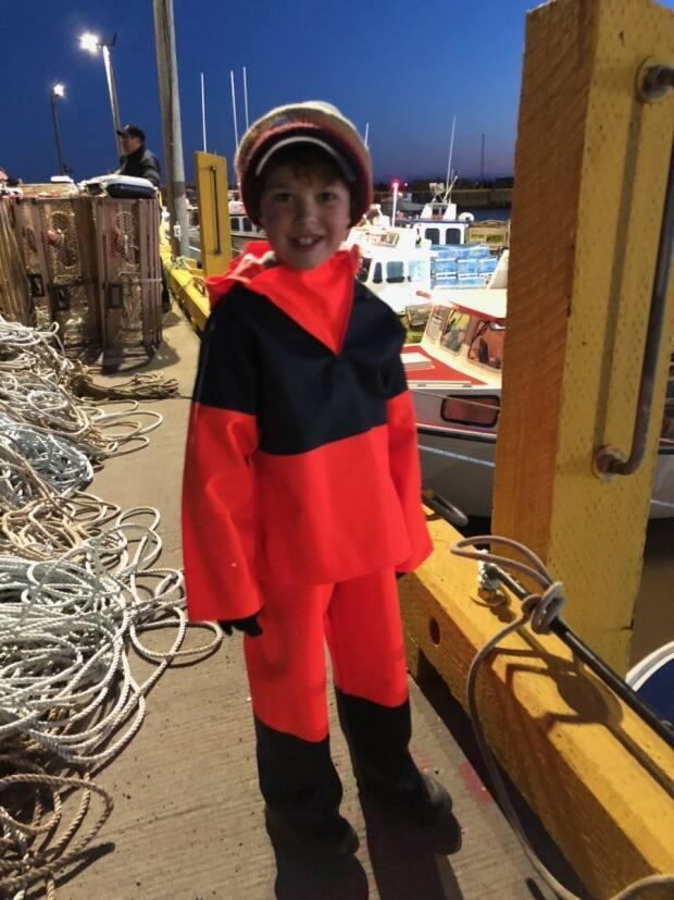 Trent Collins, dressed in the new 'oilers' fishing gear his grandfather gave him for his birthday, gets ready to head out on the boat on opening day.