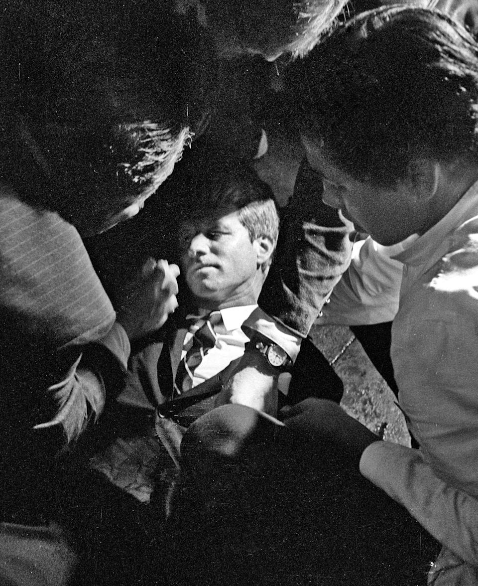 In this June 5, 1968 file photo, Hotel busboy Juan Romero, right, comes to the aid of Senator Robert F. Kennedy, as he lies on the floor of the Ambassador hotel in Los Angeles moments after he was shot. Source: Richard Drew/Pasadena Star News via AP