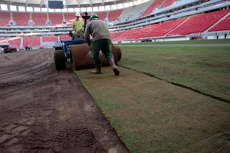 FILE - In this April 29, 2013 file photo, employees rollout lawn turf at the National Stadium during reconstruction of the stadium in Brasilia, Brazil. No matter how well Brazil does hosting the Confederations Cup, it will be hard to say the country succeeded in its preparations. There were delays and cost overruns in stadiums across the country, few infrastructure projects were completed and the nation's capacity to host the tournament was put in doubt several times. (AP Photo/Eraldo Peres, File)