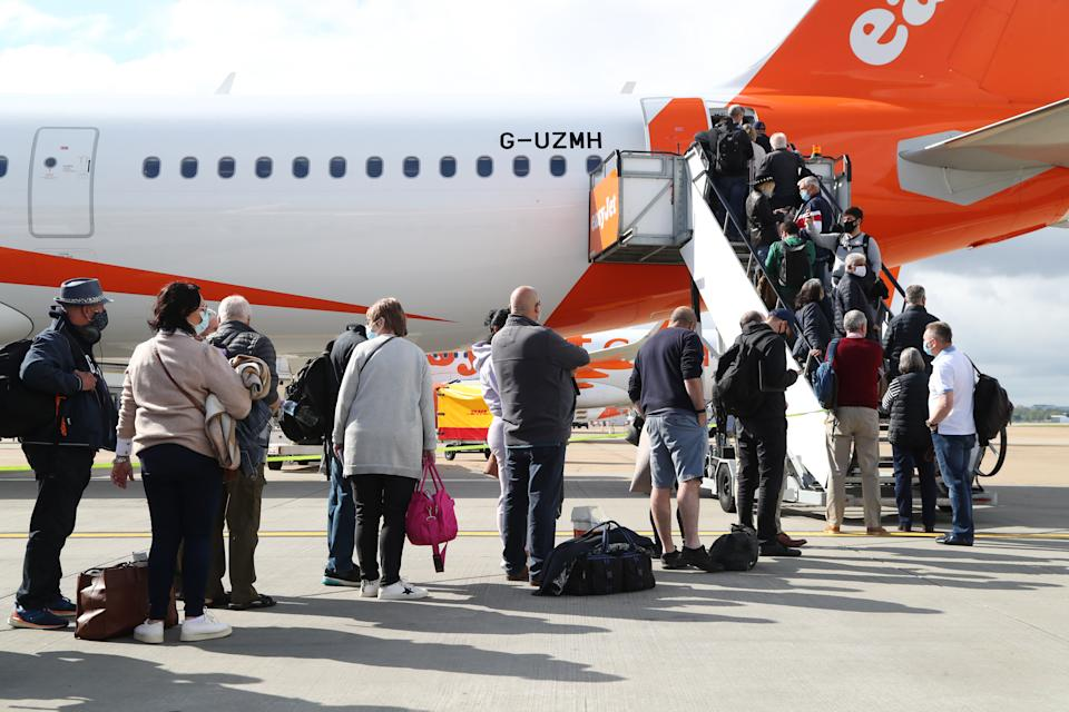 Passengers prepare to board an easyJet flight to Faro, Portugal, at Gatwick Airport in West Sussex after the ban on international leisure travel for people in England was lifted following the further easing of lockdown restrictions. Picture date: Monday May 17, 2021. (Photo by Gareth Fuller/PA Images via Getty Images)