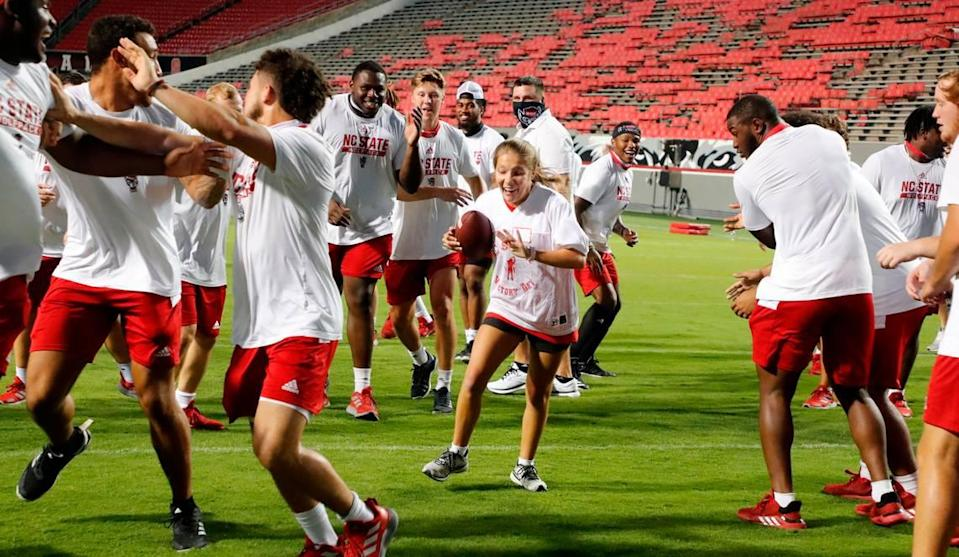"""N.C. State football players clear a path for Grace Chalker as she runs for a touchdown during """"Victory Day"""" with the Wolfpack at Carter-Finley Stadium in Raleigh, N.C., Saturday, August 7, 2021. The Wolfpack partnered with GiGi's Playhouse Raleigh, a Down's syndrome achievement center, to let participants enjoy a game day experience with players."""