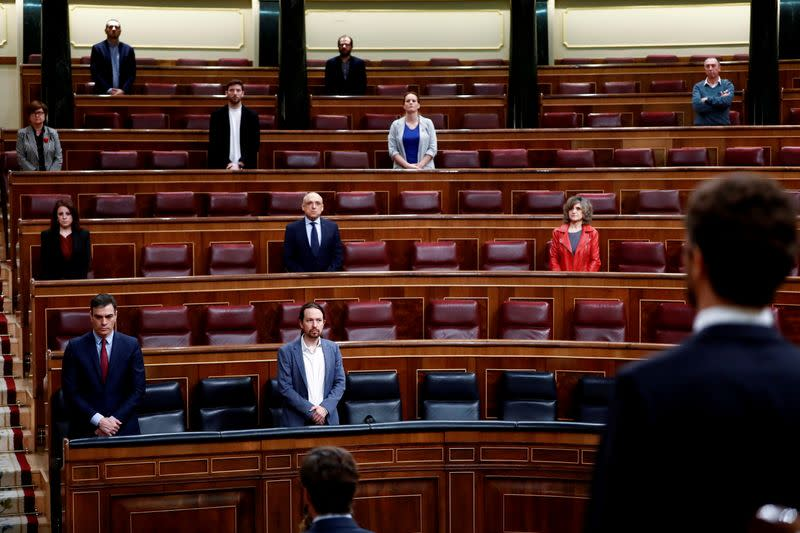 Spanish PM Sanchez and deputies stand up during a minute of silence at the start of a session on coronavirus disease (COVID-19) at Parliament in Madrid