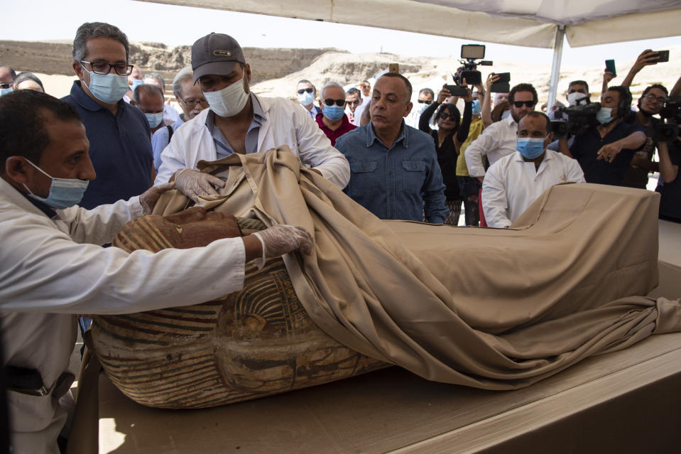 An Egyptian archaeological team opens the sarcophagus that is around 2500 years old at the Saqqara archaeological site, 30 kilometers (19 miles) south of Cairo, Egypt, Saturday, Oct. 3, 2020. Egypt says archaeologists have unearthed about 60 ancient coffins in a vast necropolis south of Cairo. The Egyptian Tourism and Antiquities Minister says at least 59 sealed sarcophagi with mummies inside were found that had been buried in three wells more than 2,600 years ago. (AP Photo/Mahmoud Khaled)