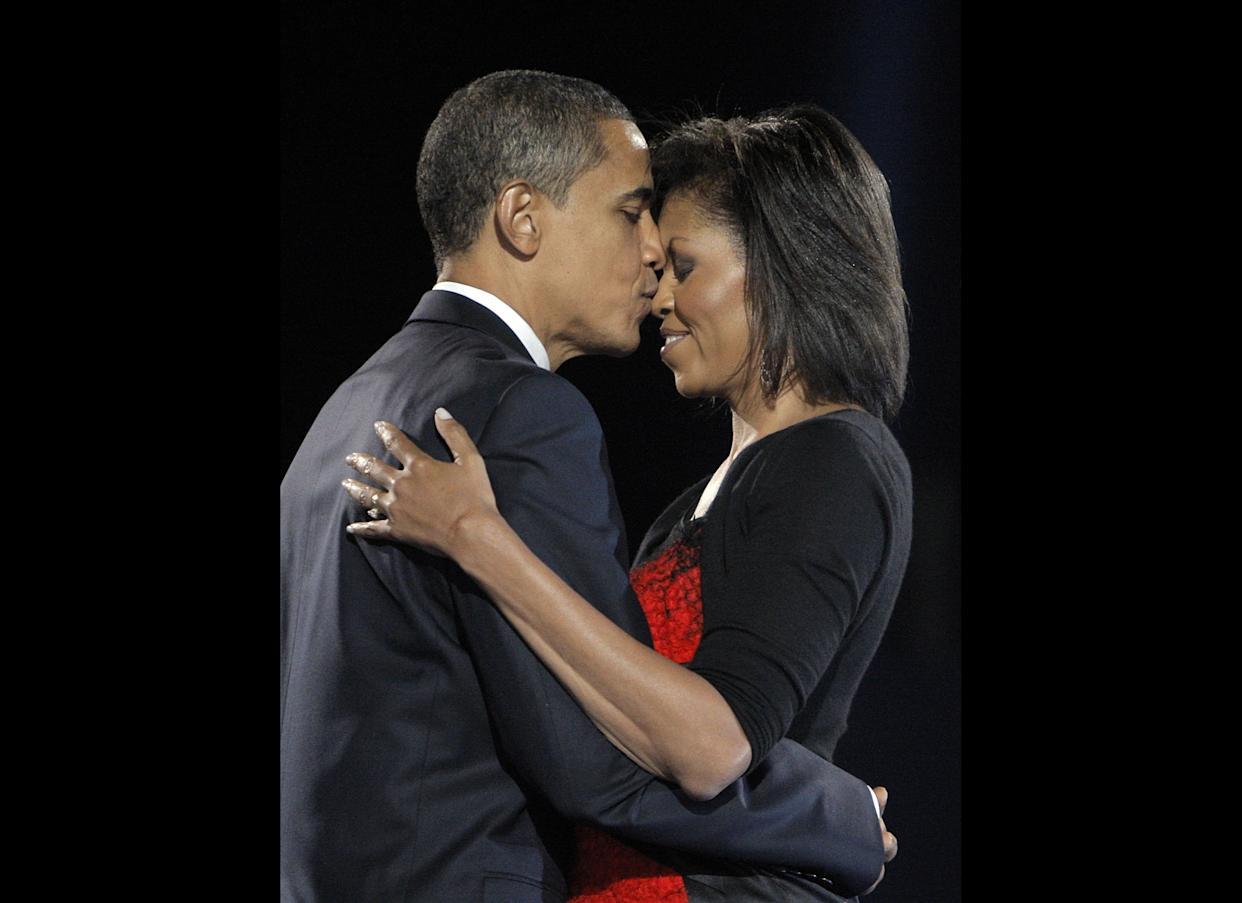 In this Nov. 4, 2008 file photo, President-elect Barack Obama, left, kisses his wife Michelle Obama after addressing supporters at the election night rally in Chicago.