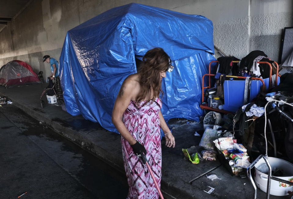 FILE - In this Oct. 19, 2018, file photo, a homeless woman, who only went by the name Angel, sweeps up the street by her tent under a freeway overpass in downtown Los Angeles. A federal judge has ordered Los Angeles city and county to move thousands of homeless people who are living near freeways, saying their health is at risk from pollution and the coronavirus. (AP Photo/Richard Vogel, File)