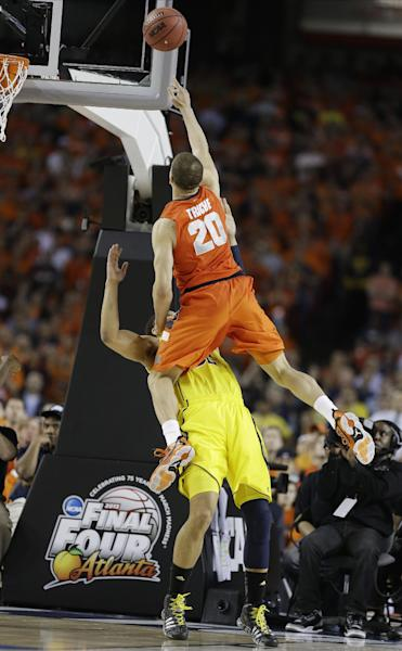 Syracuse's Brandon Triche (20) charges into Michigan's Jordan Morgan (52) during the second half of the NCAA Final Four tournament college basketball semifinal game Saturday, April 6, 2013, in Atlanta. Triche was called for charging. (AP Photo/Charlie Neibergall)