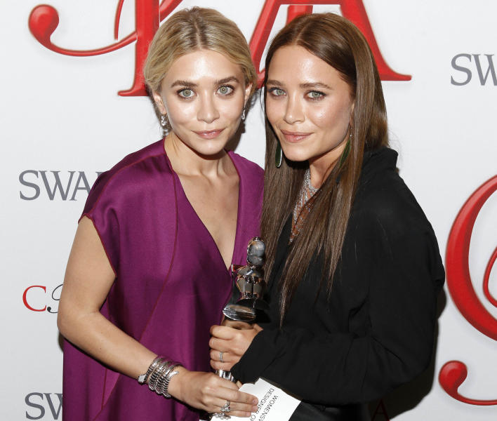 Ashley Olsen, left, and Mary Kate Olsen, designers of The Row, pose backstage after winning Womenswear Designer of the Year at the CFDA Fashion Awards on Monday, June 4, 2012 in New York. (Photo by Jason DeCrow/Invision/AP)