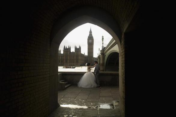 Newlyweds pose for photographs underneath Westminster Bridge in London March 10, 2012.