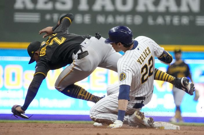 Pittsburgh Pirates' Erik Gonzalez can't handle the throw as Milwaukee Brewers' Christian Yelich slides safely into second for a two-run scoring double during the seventh inning of a baseball game Friday, June 11, 2021, in Milwaukee. (AP Photo/Morry Gash)